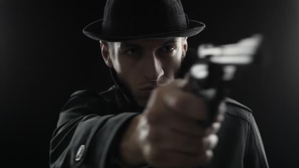 Gangster mit Hut und schwarzem Mantel. Mafioso zielt mit Waffe in die Kamera