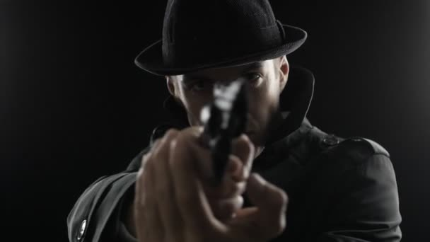 Porträt eines Gangsters mit Hut und schwarzem Mantel zielt mit Revolver