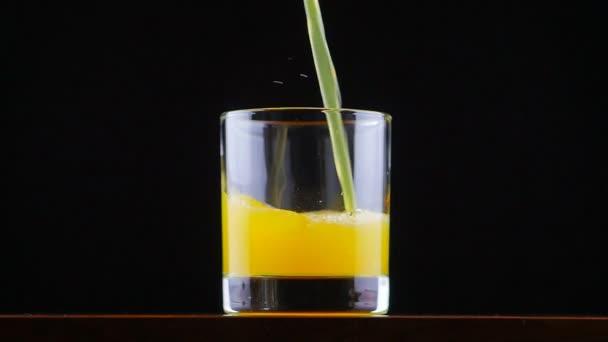Orangensaft-Limo in Zeitlupe ins Glas gießen