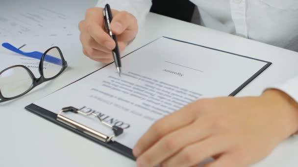Mann liest und unterschreibt den Vertrag
