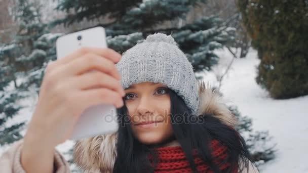 Fiatal csinos lány téli park csinál selfie, az ő okostelefon