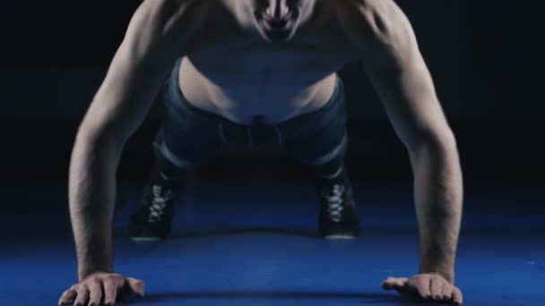 Male athlete doing push-ups in the hall