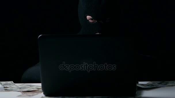 A hacker in a balaclava counts money. Cyber crime.