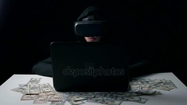 Hacker in the helmet of virtual reality work in dark room. He counts money. Cyber crime.