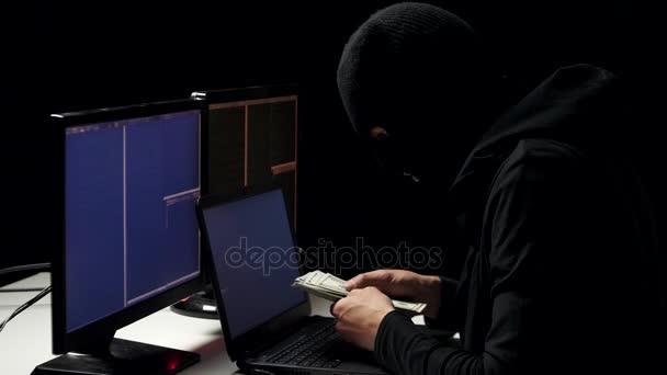 Hacker a balaclava cracking codice utilizzando laptop e computer dalla sua stanza scura hacker