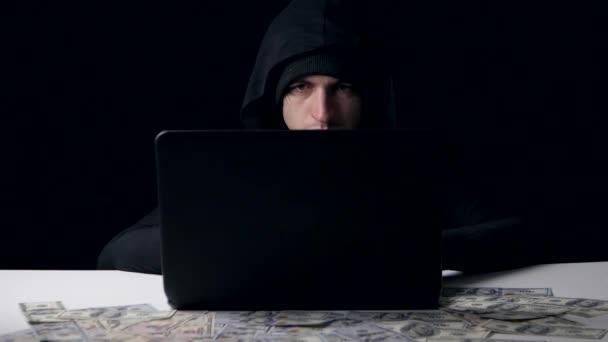 A hacker in a hood earns money. Cyber crime.