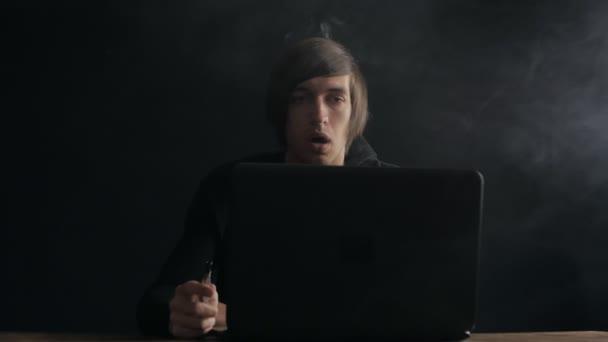 Muži, kteří pracují na notebooku a Exhaling kouř z zvlhčovač vzduchu v pomalém pohybu