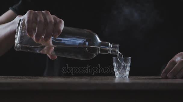 Pojem alkoholismus. Muž nalévá alkohol do sklenice a pije v temné místnosti v zpomalený