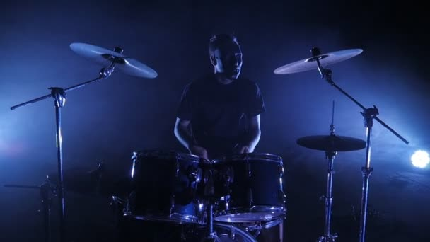 The drummer plays the drum set on the stage. Shot in a slow motion. Music video punk, heavy metal or rock group.
