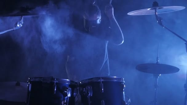 The epic footage with a male drummer in a mask is surrounded by smoke playing on a drum set in slow motion. Musical video of rock, punk, heavy metal band.