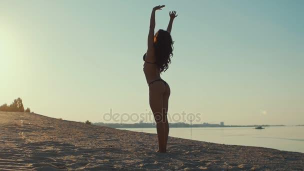 Dívka se sexy tělem stojí na pláži za úsvitu. Mladá šťastná žena stojící v písku a táhnoucí proti moři. Začátek dobrý den