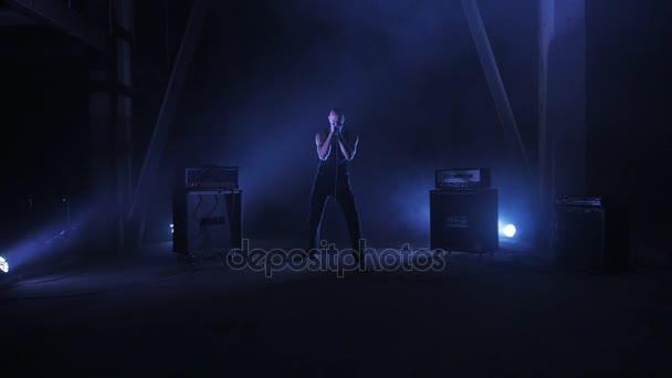 A brutális énekes rock zenekar a mikrofonba énekel. Music video punk, rock, hardcore, heavy metal együttes. A steadicam lövés