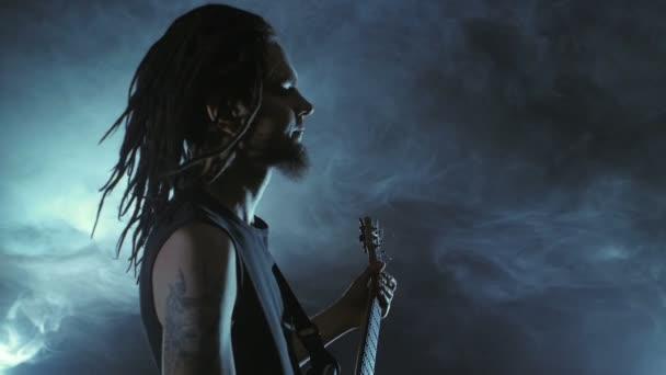 Kytarista rocker s dredy hrát na elektrickou kytaru na jevišti. Výkon hudební video rock, punk, heavy metalové kapely v pomalém pohybu.