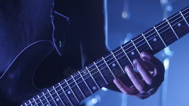 Close up of Guitarist playing the electric guitar on stage. Performance music video rock, punk, heavy metal band.