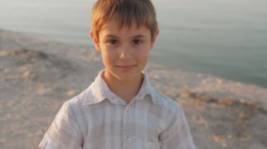 Portrait of a 10 year old boy smiling on a summer beach at sea on a background at sunset