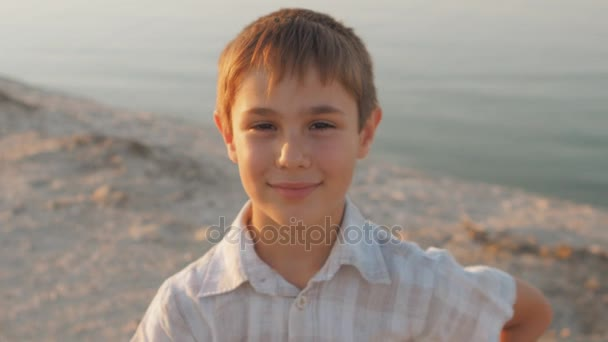 Portrét 10 letého chlapce, usmívající se na pláži v létě na moři na pozadí při západu slunce