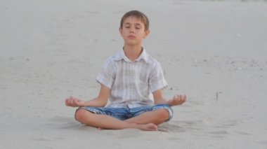 Boy meditating sitting on the sand on the beach in summer