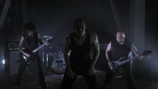Concert rock band performing on stage with Frontman, guitarists and drummer. Music video punk, heavy metal or rock group.
