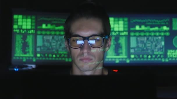 Hacker programátor v brýlích pracuje v centru zabezpečení cyber plné obrazovky v počítači