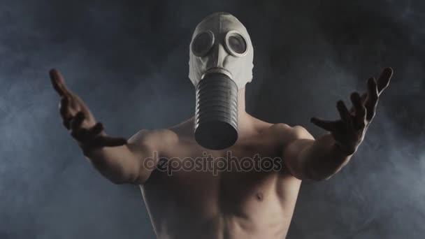 zblízka portrétní nahého muže v plynové masce rozšiřuje jeho paží vpřed v zakouřené tmavé místnosti