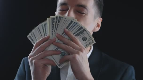 young businessman with a lot of dollar bills is happy about profit or salary