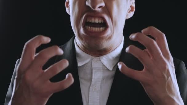 agresszív üzletember öltönyt sikoltozik, és mutatja a harag a fekete háttér. Dühös főnök. A veszély az erőszak