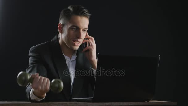 young businessman working on laptop and doing exercises with dumbbells