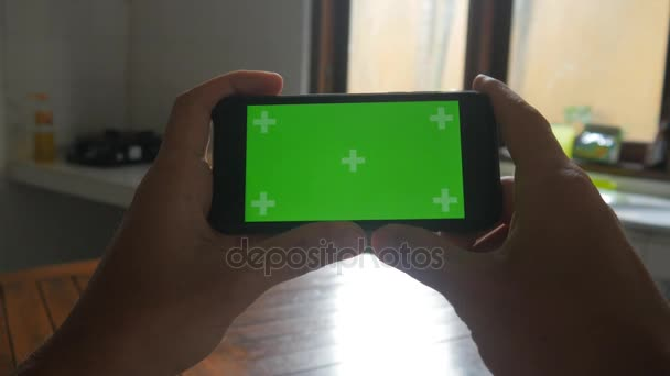 Close-up of male hands touching of smartphone in the kitchen. Green screen Chroma Key.