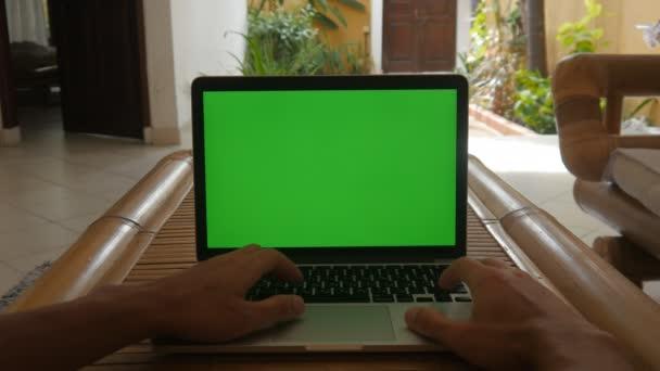 Ember dolgozik a laptop otthon zöld képernyő. Szabadúszóként dolgozik otthon.