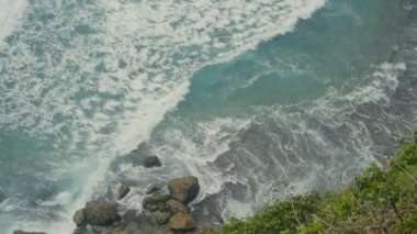 Ocean waves breaking on the stone cliffs. Aerial top view of Tropical beach Bali, Indonesia. Slow motion