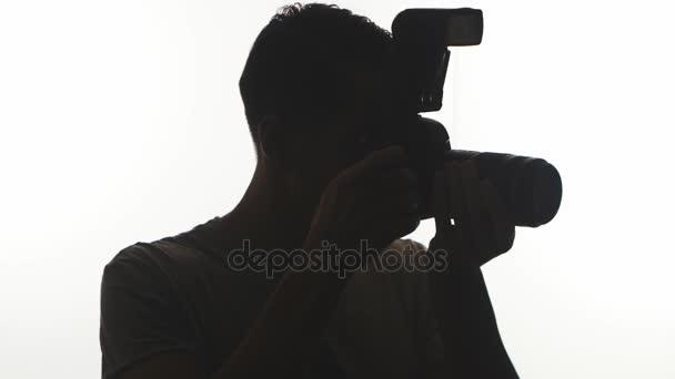 Sagoma del primo piano del fotografo. Giovane che prende le immagini con la macchina fotografica di Dslr isolato su priorità bassa bianca