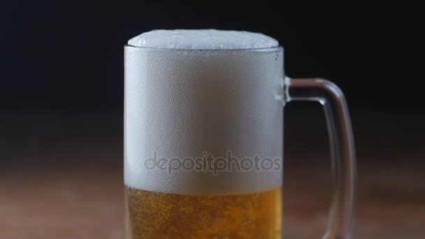 Hideg fény sör, egy pohár, fekete háttér, Lassított lejátszás