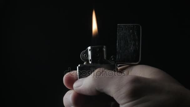 Close Up Of The Opening And Burning Iron Zippo Lighter On A Black