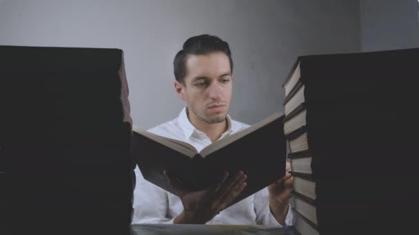 Mladý muž v bílé košili čte knihy v knihovně. Podnikatel se posouvá mezi stránkami knih. Mnoho knih na stole