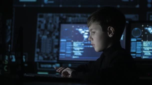 Roztomilý dospívající chlapec programátor pracuje u počítače v datovém centru plné obrazovky. Portrét zázračné dítě hackera