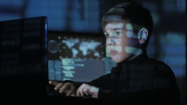 Cute teen Boy hacker programátor pracuje v centru zabezpečení cyber plné obrazovky v počítači. Binární kód na obličeji