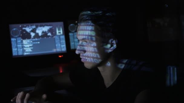 Hacker programátor v brýlích pracuje na počítači, zatímco modré kód znaků odráží na jeho tvář v cyber security centrum plné obrazovky