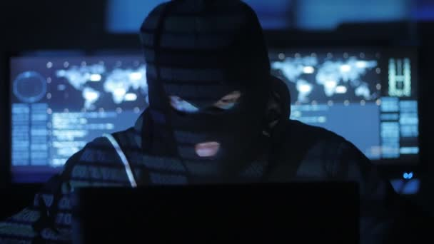 Anonymous hacker in the mask tries to enter the system using codes and numbers to find out the security password. The concept of cybercrime.