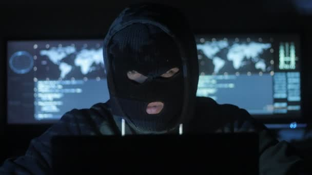 Nebezpečný hacker v masce se snaží vstoupit do systému Zjistěte bezpečnostní heslo pomocí kódů a čísel. Koncept počítačové kriminality.
