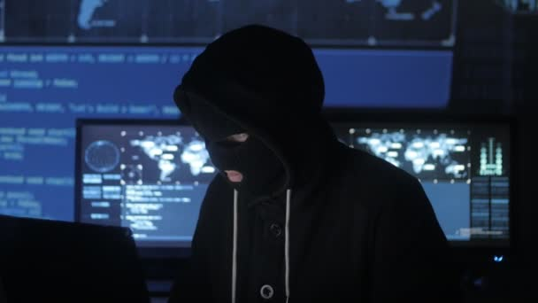 Dangerous hacker in the mask tries to enter the system using codes and numbers to find out the security password. The concept of cybercrime.