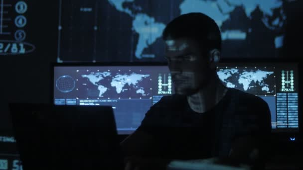 Mužské hacker programátor pracuje v počítači, zatímco modré kód znaků odráží na jeho tvář v centru zabezpečení cyber plné obrazovky