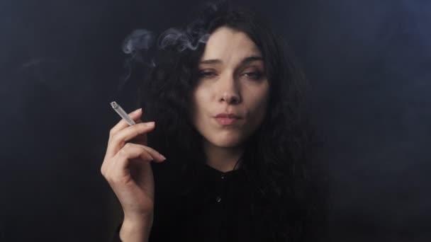 Portré, fiatal, barna nő, göndör haj, cigarettázott, és néz a kamerába, sötét füstölt szobában