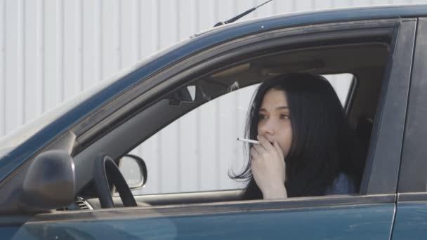 Porträt einer jungen Frau, die im Auto eine Zigarette raucht