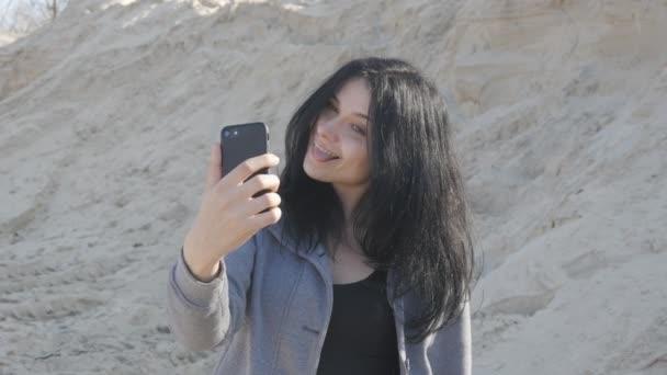 portrét Roztomilá brunetka žena dělá selfie pomocí svého smartphonu. Vítr snadno vlny její vlasy.