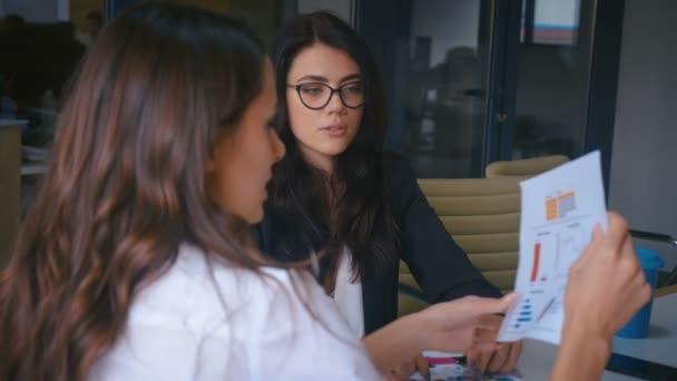 Két női munkatárs, akik irodai beszélgetéseken dolgoznak együtt a munkahelyen. Üzleti női munkatársak megvitatása üzleti projekt ötletbörze a vállalati csapatmunka.