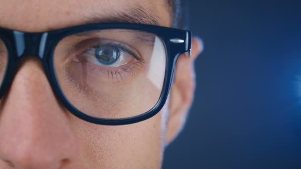 Macro blue eye of man in eyeglasses. Close up eye of businessman or student in glasses