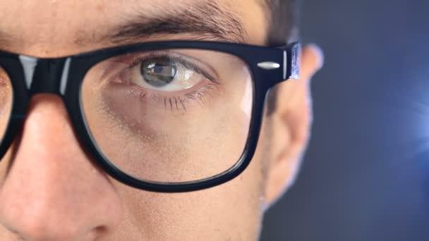 Macro blue eye of man in eyeglasses. Close up eye of businessman or student in glasses