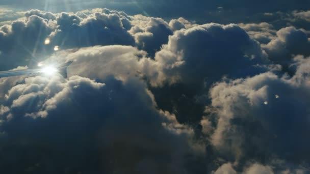 Letecký pohled nad mraky z okna letadla s modrou oblohou. pohled z okna letadla na modré nebe a bílé mraky. Cestování letadlem.