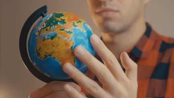 Mladý muž držící glóbus. Muž otáčí glóbus a ukazuje na něj. Koncept cestování.