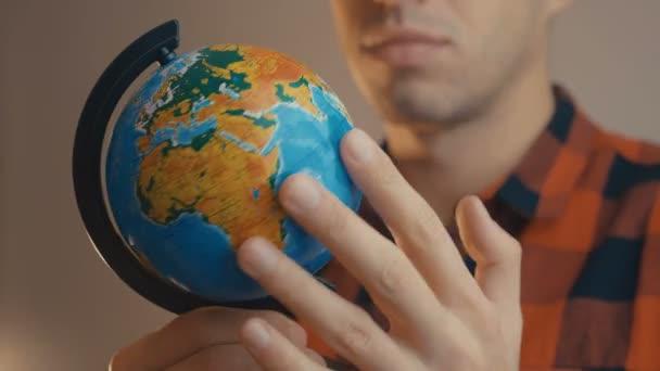 Fiatal férfi gazdaság földgömb. Az ember megpörget egy földgömböt és rámutat. Utazási koncepció.